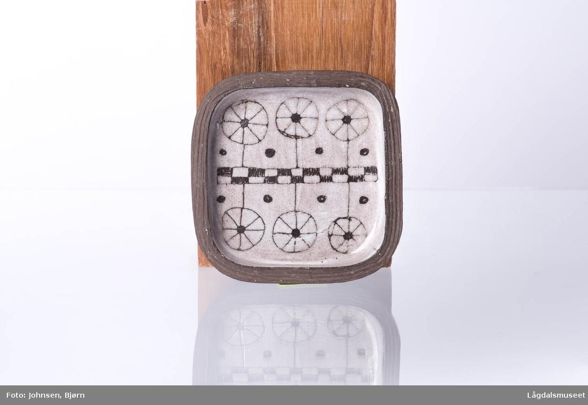 Motivet består av geomteriske figurer som danner et helhetlig bilde. Dekoren er gjort i teknikken grafitto.