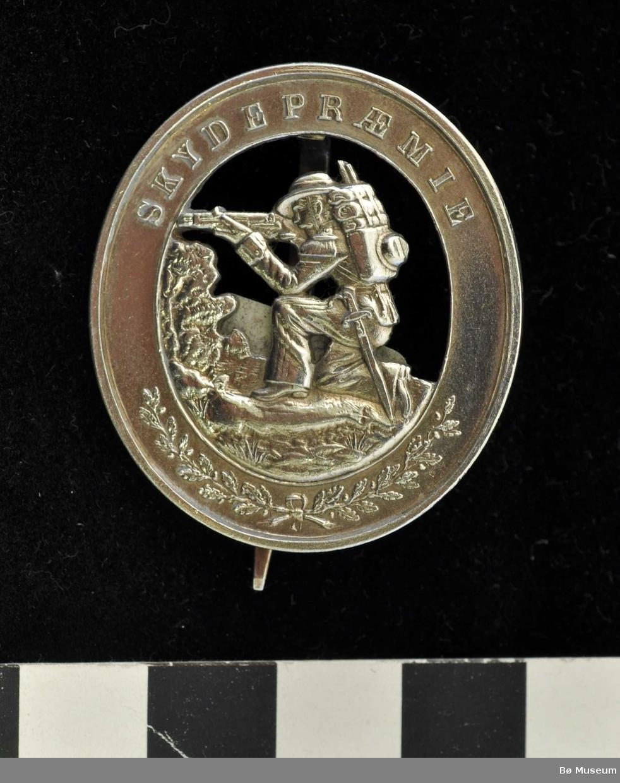 Oval medaljenål med motiv av en knestående skytter