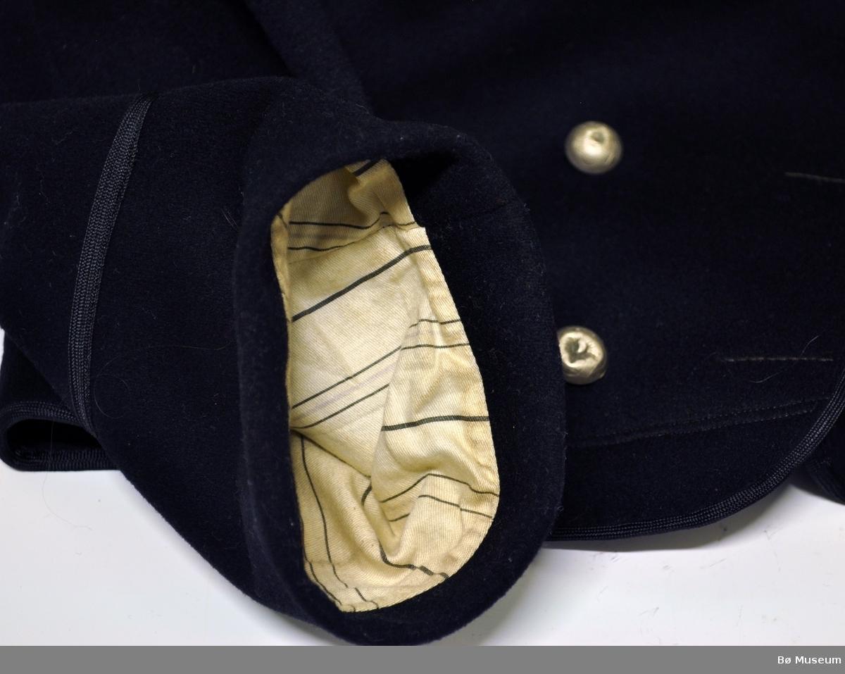 Svart,kort  jakke med krage og dobbeltknepping, 3 metall knapper på hver side. Knapphullene er ikke sydd, kun markert med håndsøm. Foran er det en lomme på hver side.Ryggen har midtsøm og søm fra skulderene og ned, samt sidesømmer. Ryggens avslutning går ned i en liten spiss på midten. Jakken er kantet med svarte bånd. Samme bånd på ermene, 9 cm opp fra emets kant. Materialet er av  klede/vadmel. Innvedig er det påsydd hempe til oppheng. Det er to stk fôr:, ermene har stripet hvitt/svart/grått sateng vevet bomullstøy og hovedfôret har samme tøy bare i svart.   Jakken tilhører vest BØB.1990:0035.