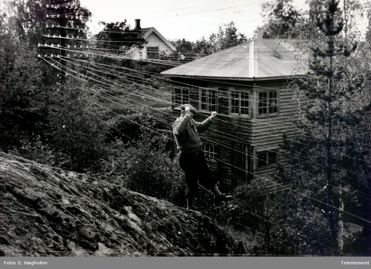 Telefonkurs i skråning med en person oppe i ledningene og et hus (funkis) i bakgrunnen. Dette er på kursen Romedal-Vallset.