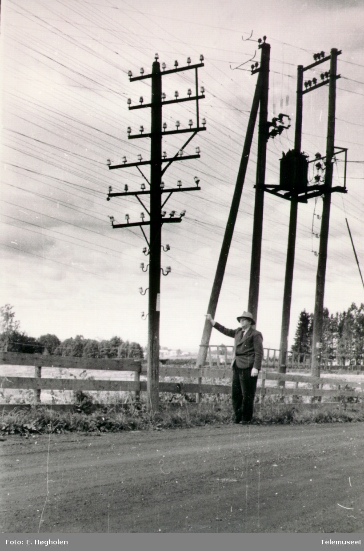 Telefonstolpe med 6 traverser og 4 par isolatorer nedover på stolpen, har kurs som krysser med E-verket ved en transformator, ved Herredsvang ved Romedal sentral.