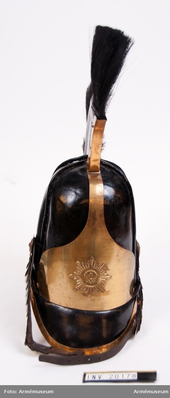 """Grupp C I. Av svart lackerat läder med svart tagelliggare och vapenplåt av mässing med Andreas Gardets stjärna. Skärm av läckerat läder med mässingsskoning. Hakrem med mässingsfjäll. Foder av grov linnelärft.  LITT  Enl. Pantschulitseffs """"Chevalier Gardets Historia"""" Del IV sidan 118 införde läderkask till Chevaliergardets uniform 1803 och var i bruk till år 1845 (Del IV sidan 128). Enl.""""Handbuch der Uniformenkunde"""", Knötel-Sieg, sidan 322, ha båda första gardeskavalleriregementerna Andreas-Gardet stjärna på kasken."""