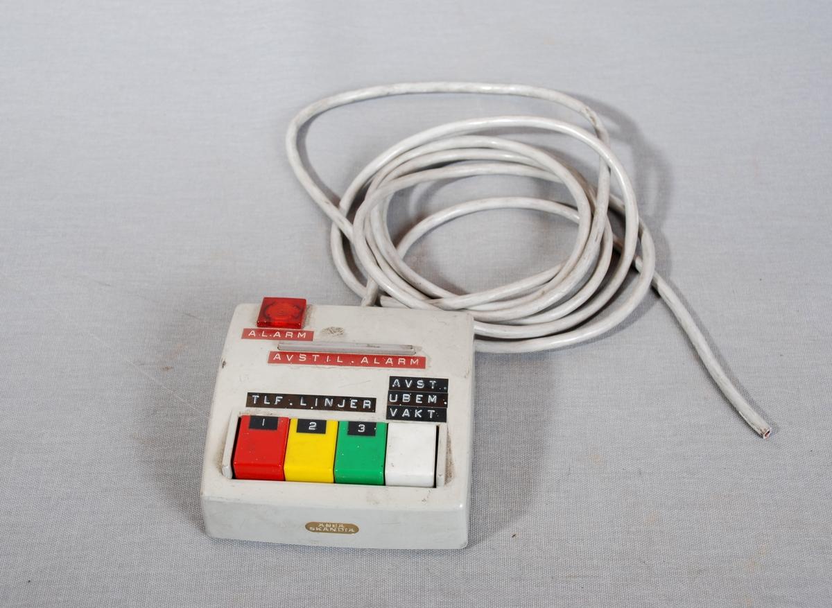 firkantet boks med 4 taster i ulik farge, tre av dem er nummerert som telefonlinjer, den fjerde merket for ubemannet vakt . Alarmlys øverst og avlang avstillingsknapp for alarm nedenfor. Kabel festet i bakkant. Kontakt er avklippet i andre enden.