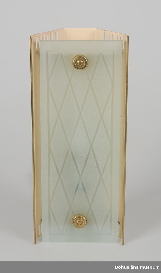Tresidigt formad lampa (stående rektangulär) med bredaste sidan utåt. Beigefärgad plåt och med matt, etsat glas framtill på bredaste stället. Glaset med matt yta och etsad dekor av korsande linjer. Glaset fastsatt med två dekorativa mässingsskruvar. Vit, plastomsluten sladd.  Från brukarens arbetsrum.                                                    Personuppgifter och fakta kring samlingen se UM025572.
