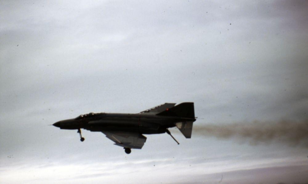 Lufthavn/Flyplass. Et amerikansk jagerfly av typen McDonnell Douglas Phantom, kommer seilende og passerer i lav høyde.