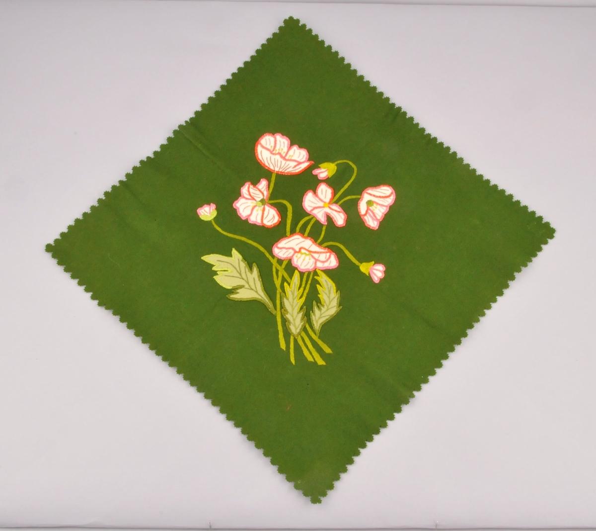 Grøn kvadratisk lita brikke av klede med rosa og kvitt broderi med blomstermotiv. I applikasjon og silkebroderi. Klipte  tunger rundt kantane.