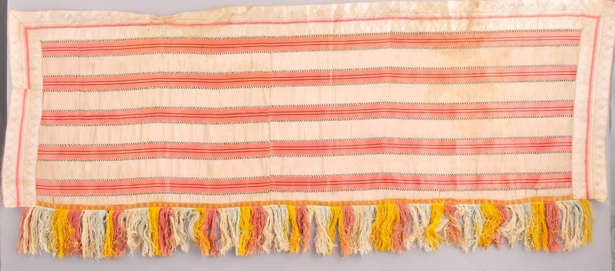 Hylk der rettsida er av stripet silkestoff i rosa, gulkvitt og brunt. På eine langsida påsett eit silkeband med tafs i ecru, grått, gult og rosa. Dei to kortsidene og andre langsida er påsett silkeband i gulkvitt og rosa med siksak-mønster. Baksida er eit mønstra kattunstoff, blad og blomemønster i fleire fargar på gulkvit botn.