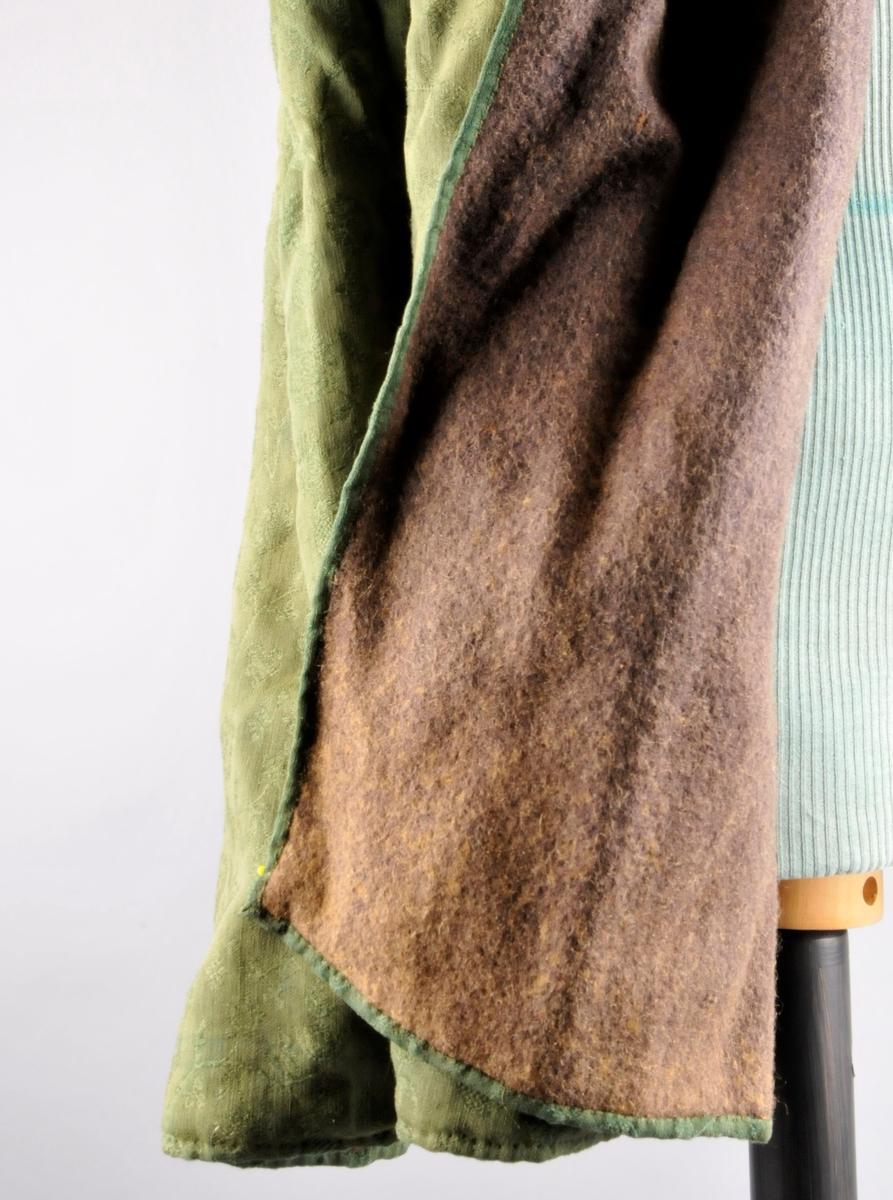 Kjeringkåpe av grøn ulldamask. Kåpa er samansauma av to breie og ei smal stoffbreidde; klipt trådrett, og som er foldelagde oppe ved halslina og har motfold midt bak, alle legg (20 tilsaman) ligg mot midt på skulder. Fóret er einsfarga blått verken (lin og ull). I ytterkantane er ytterstoffet bretta  dobbelt over til vranga og sydd til med faldesting/prikkesting gjennom alle lag (dannar stikning på rettsida). I nedrekanten på ytterstoffet er det spor etter eit påsauma band (stoffet er mørkare og trådendar sit att på vranga).