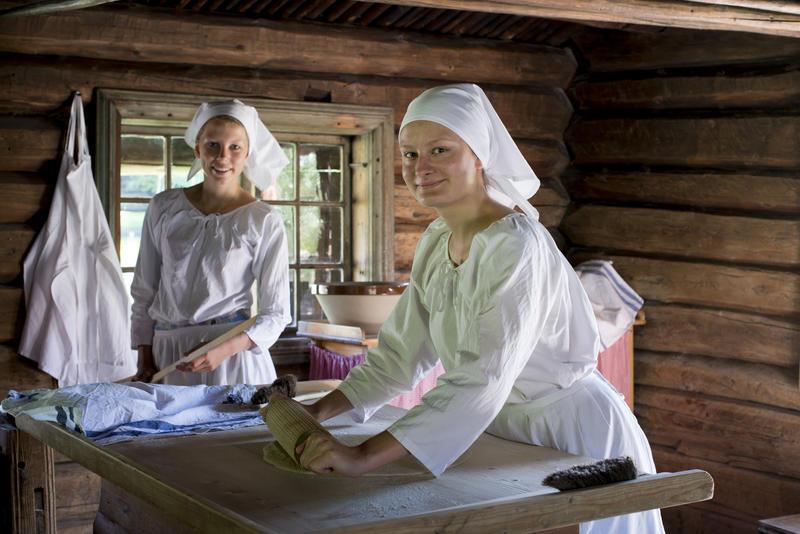 To kvinner baker lefser i eldhus