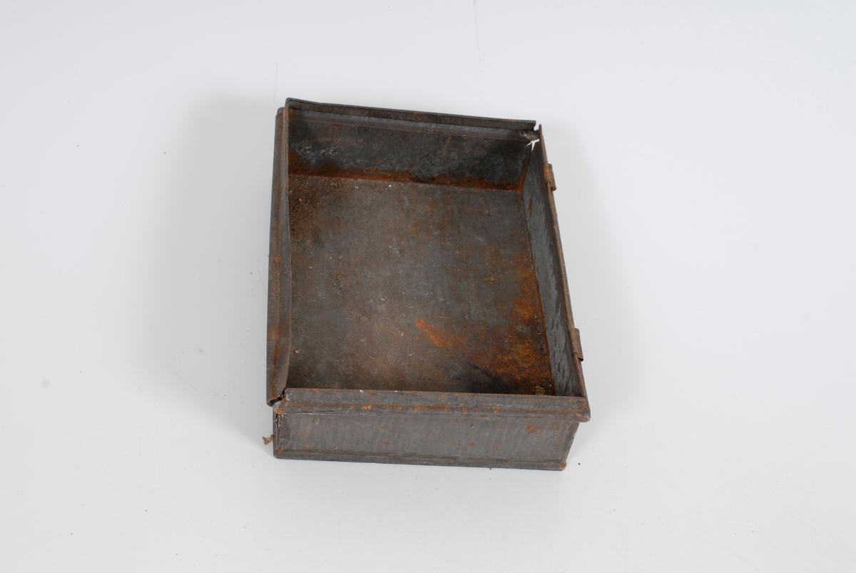 Form: Metalleske / skuff med fire børster, et rundt etui med skopuss, og to pussefiller.