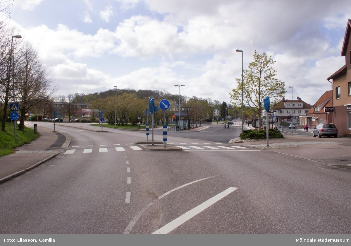 Korsningen Gamla Riksvägen och Streteredsvägen i Kållered Centrum. Till vänster ligger Vommedalsområdet i rött tegel. Det vita huset till höger innehåller lägenheter samt en servicebutik i entréplan. Längre till höger ligger en trappa som går under järnvägen. Vidare ser man Kållereds vårdcentral samt en butiks- och lägenhetsbyggnad med Second Hand.