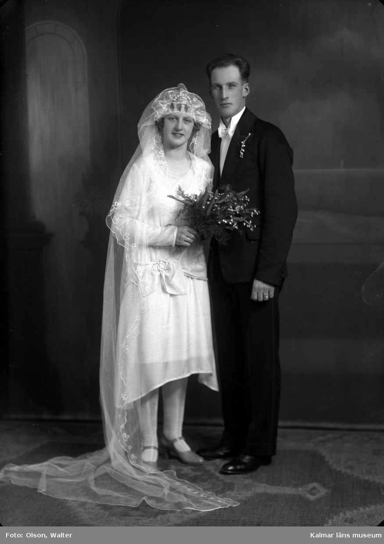 Bröllopsfoto av ett par. Kvinnan har slöja och håller i en blombukett. Mannen har kostym. Enligt Walter Olsons journal är bilden beställd av Artur Johansson ifrån Lindölundsgatan 14 i Kalmar. Kalmar läns museum känner inte till om det är den personen som är avporträtterad.