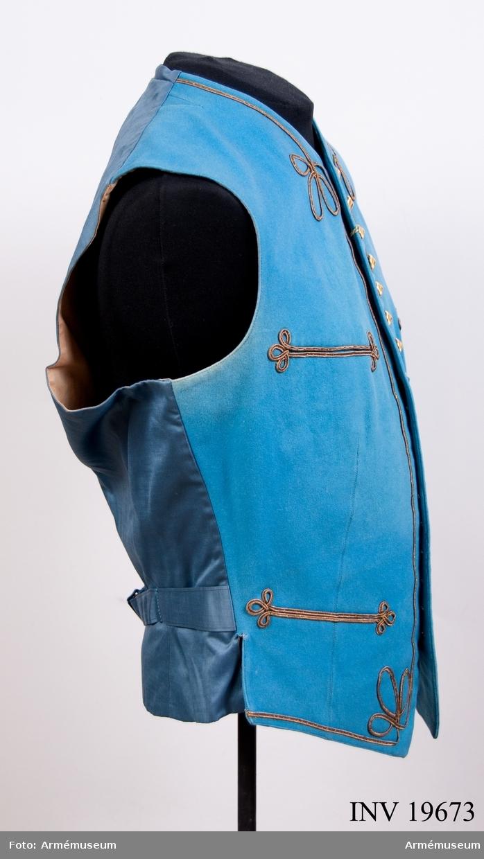 Mässväst för bruk vid Karlberg. Västen är av blått stampat kläde och har snörmakerier i guld och artilleriknappar.  Västen har burits av Carl-Reinhold von Essen född 1891, tidigare överstelöjtnant vid Svea artilleri regemente A 1.  Mässvästen är inte fastställd av armén.