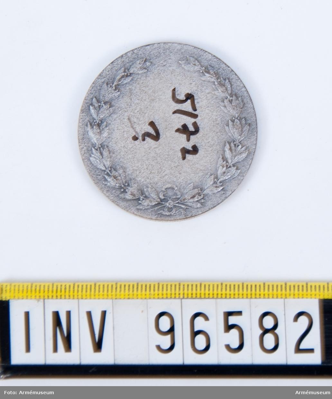 Medalj i silver för Skånska kavalleriregementet. Stans 20963, härdad 1949-09-08. Medalj, åtsida med strålformig stjärna med 2 regementsfanor, den ena med skånska gripen samt inskr. LANDSKRONA 1677, PULTUSK 1703, POSEN 1704, FRAUSTADT 1706, med tre kronor krönt av kungl. krona som fanspets. Den andra med svärd och kunglig krona samt 4-armat kors jämte inskr. BORNHÖFT D. 7 DEC. 1813 samt med kronor i hörnen med Gustaf V:s namnchiffer som fanspets, inom omskrift KUNGL. SKÅNSKA KAVALLERIREGEMENTET. Modell: Åke Hammarberg.