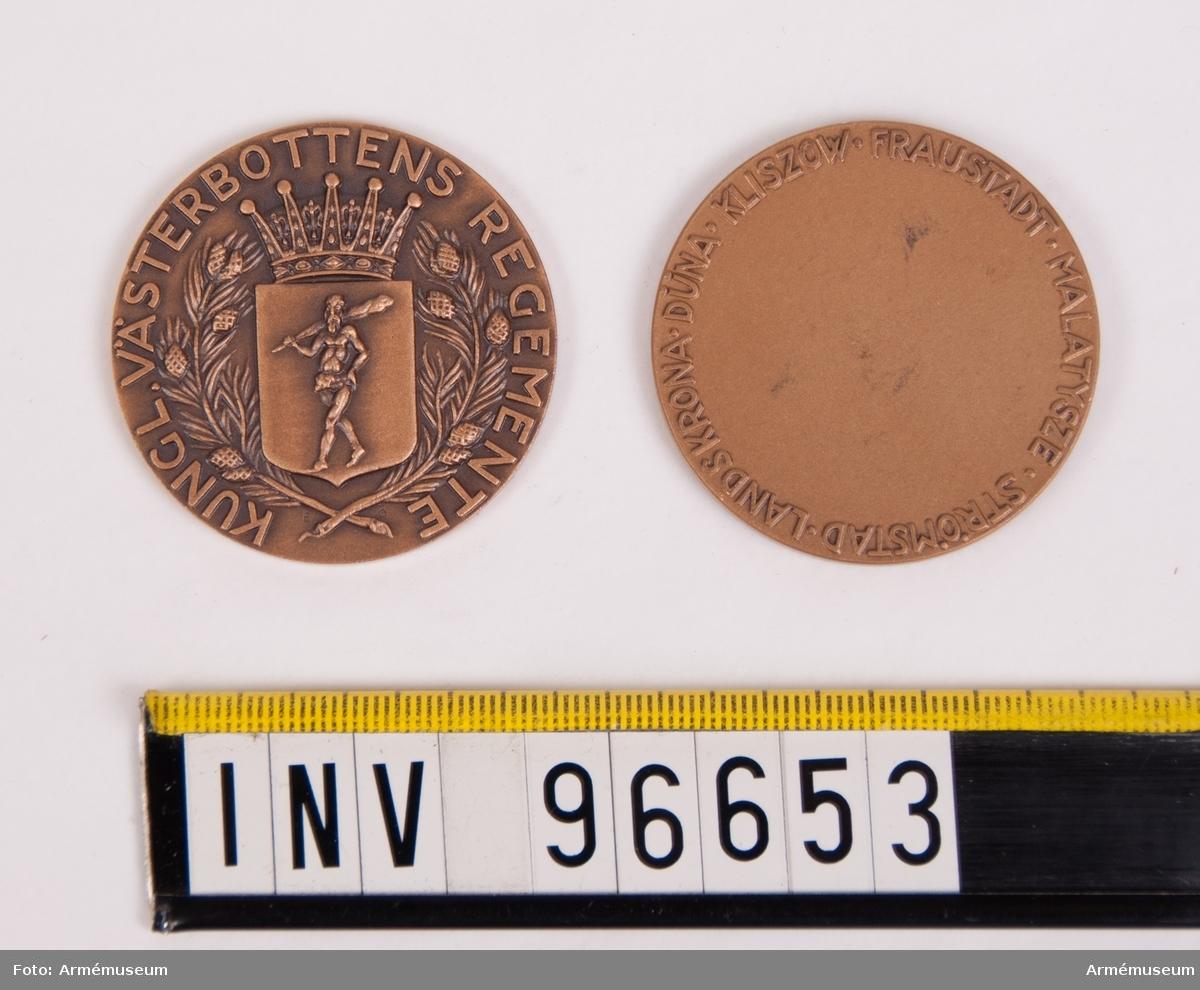 Medaljer i brons för Västerbottens regemente. Medalj, åtsida sköld med Västerbottens regementes vapen, krönt av hertiglig krona, omgivet av tallkvistar, inom omskrift KUNGL. VÄSTEROTTENS REGEMENTE. Frånsida med inskription runt kanten FRAUSTADT MALATYSZE STRÖMSTAD LANDSKRONA DUNA KLISZOW, enligt modell av Eugen Örnsäter. Stans nr 7532, 7533. Stans härdad 1933-04-05.