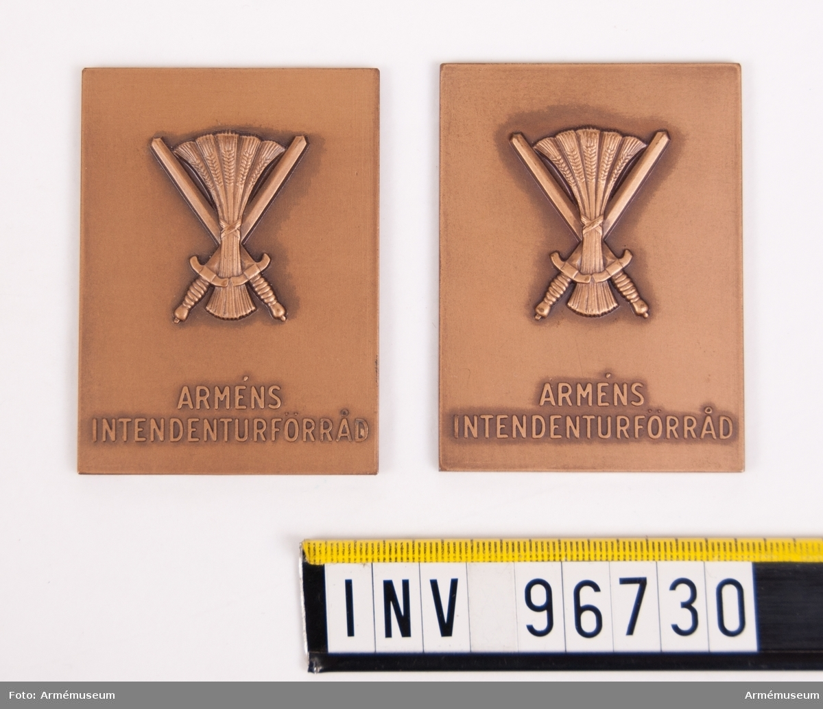 Plaketter i brons för Arméns intendenturförråd.  Plakett, åtsida med intendenturemblemet jämte inskription ARMÉNS INTENDENTURFÖRRÅD. Den ena plaketten med textprov på baksidan; H B G EKFELDT A I S 1940-1961. Stans nr 4635. Stans härdad 1961-01-18.
