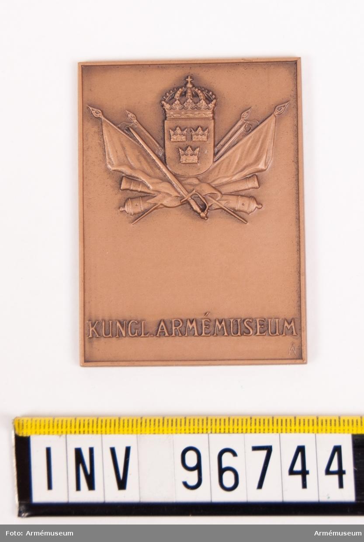 Plakett i brons för Armémuseum. Plakett upptagande sköld med tre kronor , krönt av kunglig krona på krysslagda fanor och kanoner jämte sabel, med text nedtill KUNGL. ARMÉMUSEUM. Stans nr 5811. Stans härdad 1950-05-22.