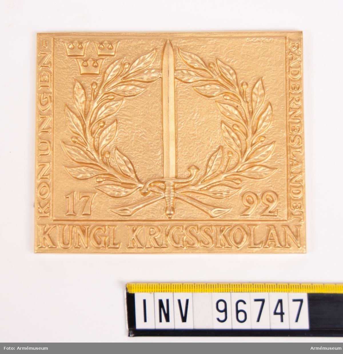 Plakett i guld för Kungliga krigsskolan. Plakett med svärd, kvistar samt 3-kronor jämte inskr. KUNGL KRIGSSKOLAN KONUNGEN - FÄDERNESLANDET 1792, efter modell av skulptör Åke Hammarberg. Stans nr 28769. Stans härdad 1963-05-30.