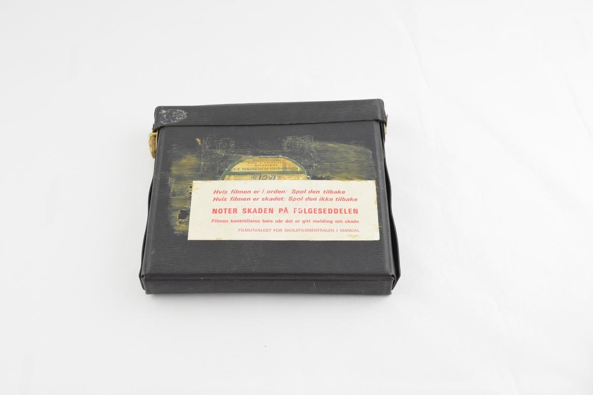 Filmrull i eske. Film på metallspole. Firkantet papir etui åpnes langs en av sidekantene. Lærreim med metallspenne.