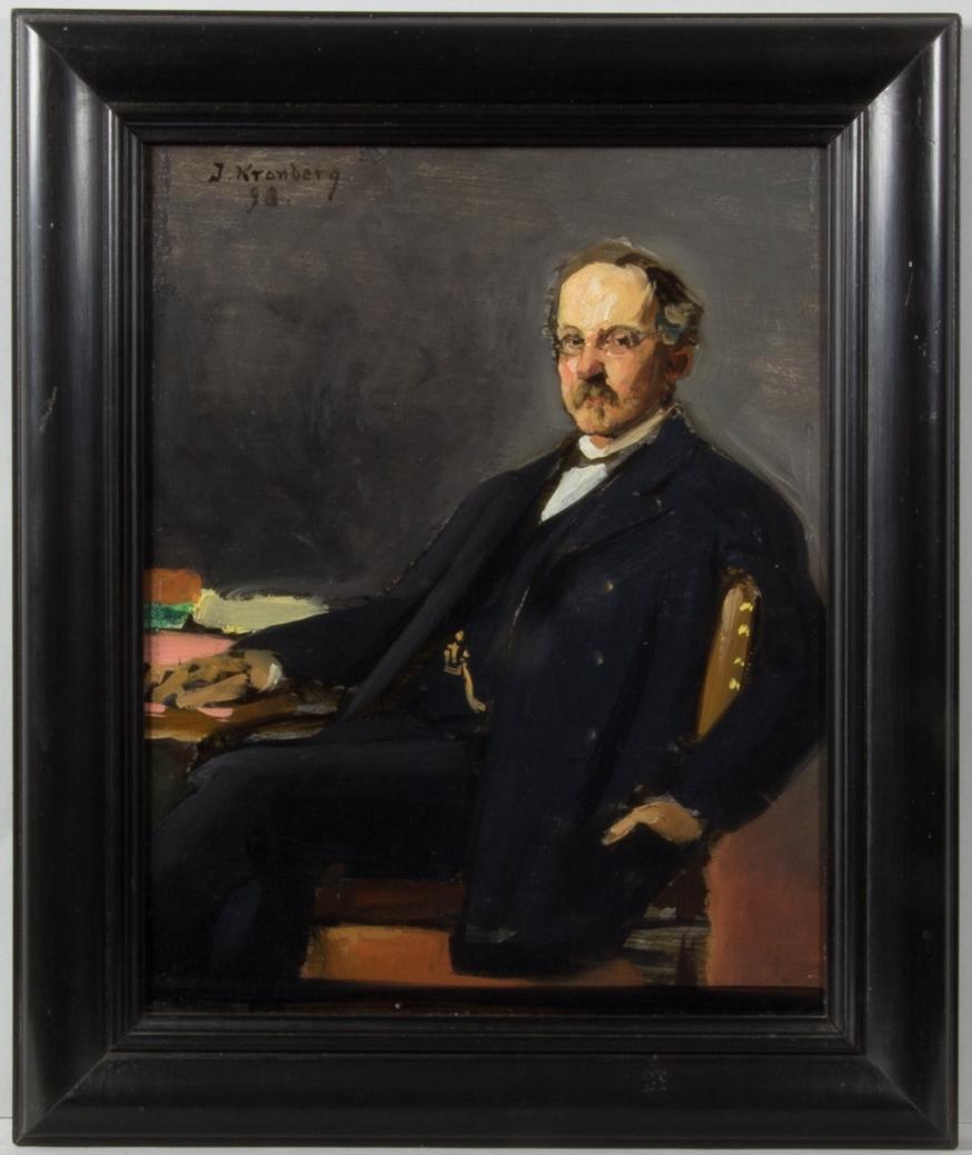 Porträttskiss föreställande Hugo Tamm, Fånö, sittande vid sitt skrivbord. Klädd i mörk kostym med väst och klockkedja. Glasögon och mustasch. Ena handen ligger på skrivbordet och den andra håller han i fickan. Mörk bakgrund.