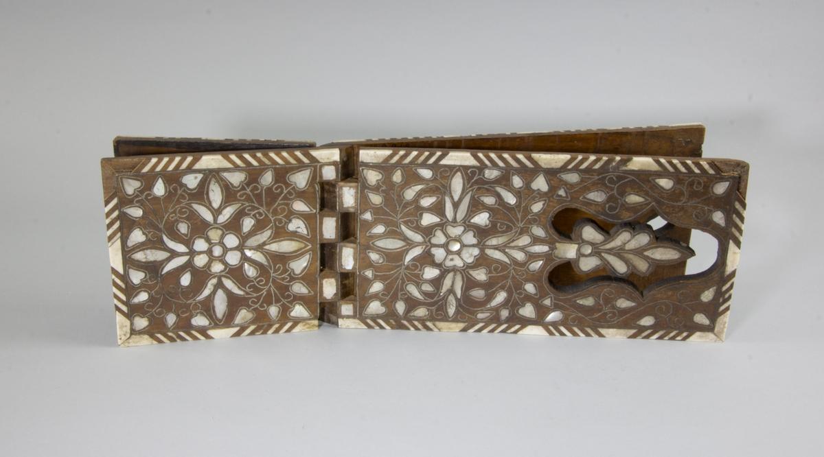 Bokstöd tillverkat av trä med rika inläggningar av vegetativ karaktär av pärlemor, ben och silver. Utformat som ett X, hopfällbart. Orientaliskt ursprung.