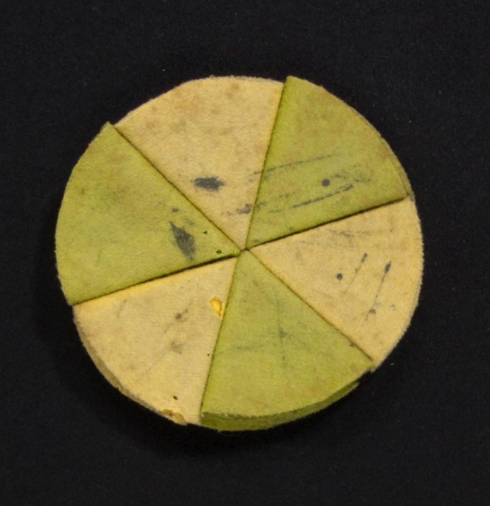 Penntorkare, rund, tillverkad av bitar av ylletyg i flera lager. Varje bit vikt i flera lager till en triangel och hopsydda med varandra. Varannan triangel grön, varannan gul och undersidan svart. Spår av användning.