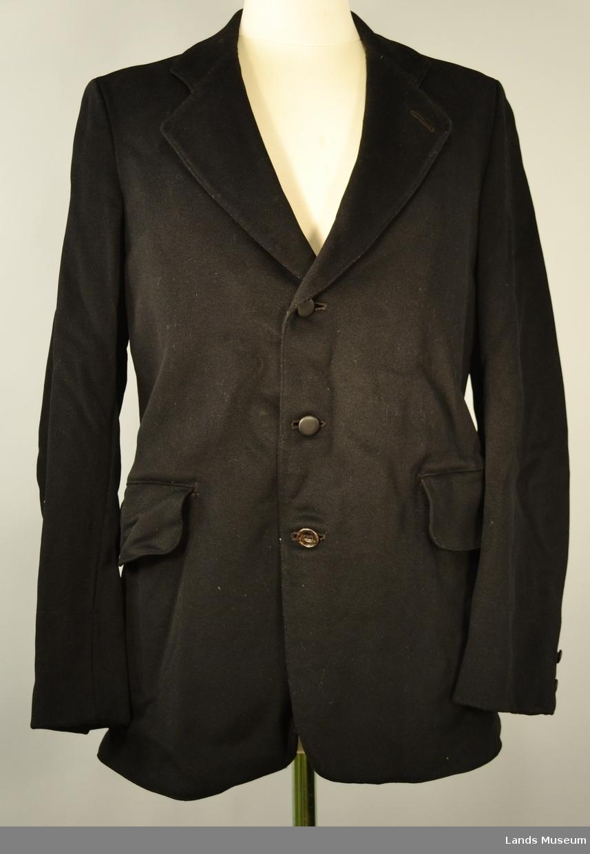 I svart klede med glanset bomullsfor. Lyst brunstripete for i erme. Tre knapper foran og to små knapper på kvart erme. To lommer, ein stikklomme og ein innerlomme i foret. Splitt bak som er i gjensydd. Skreddersydd.