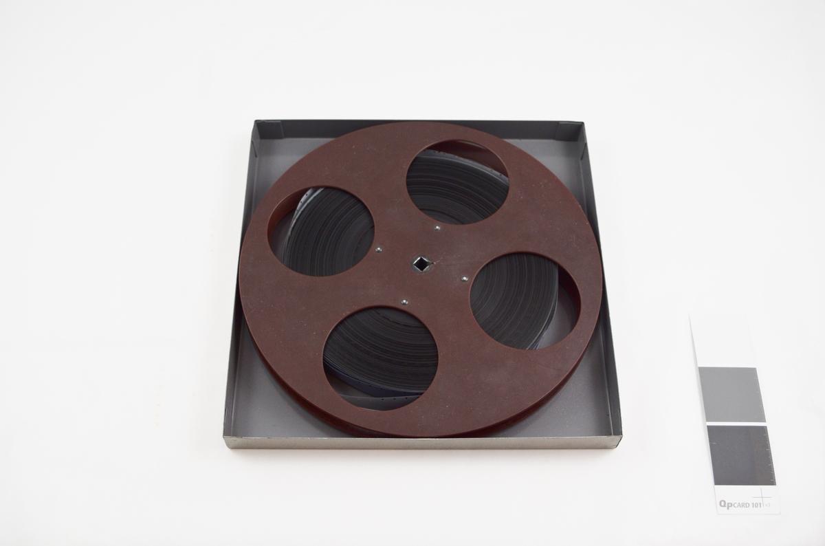 Filmrull i eske. Film på plastspole. Kvadratisk metalletui i to løse deler: bunn og lokk.