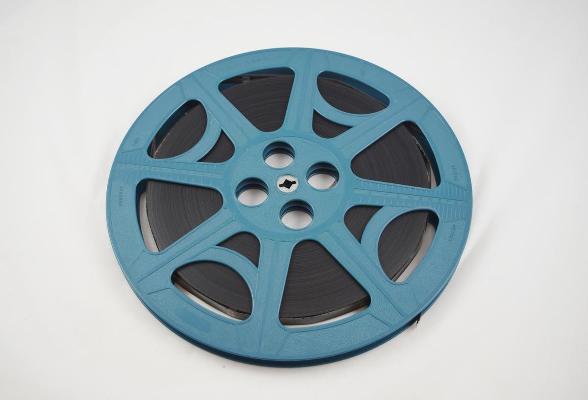 Filmrull i eske. Film på metallspole. Kvadratisk papiretui i to deler, lukkes langs den ene siden ved hjelp av lærreimer og metallspenner.