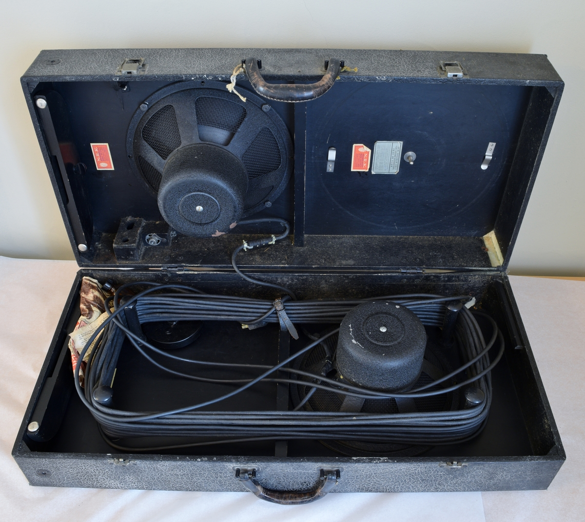 Høyttalersett til videofremviser. To stk. høyttalere pakket sammen som en koffert. Inneholder også smøreolje som var pakket inn i et ukeblad.