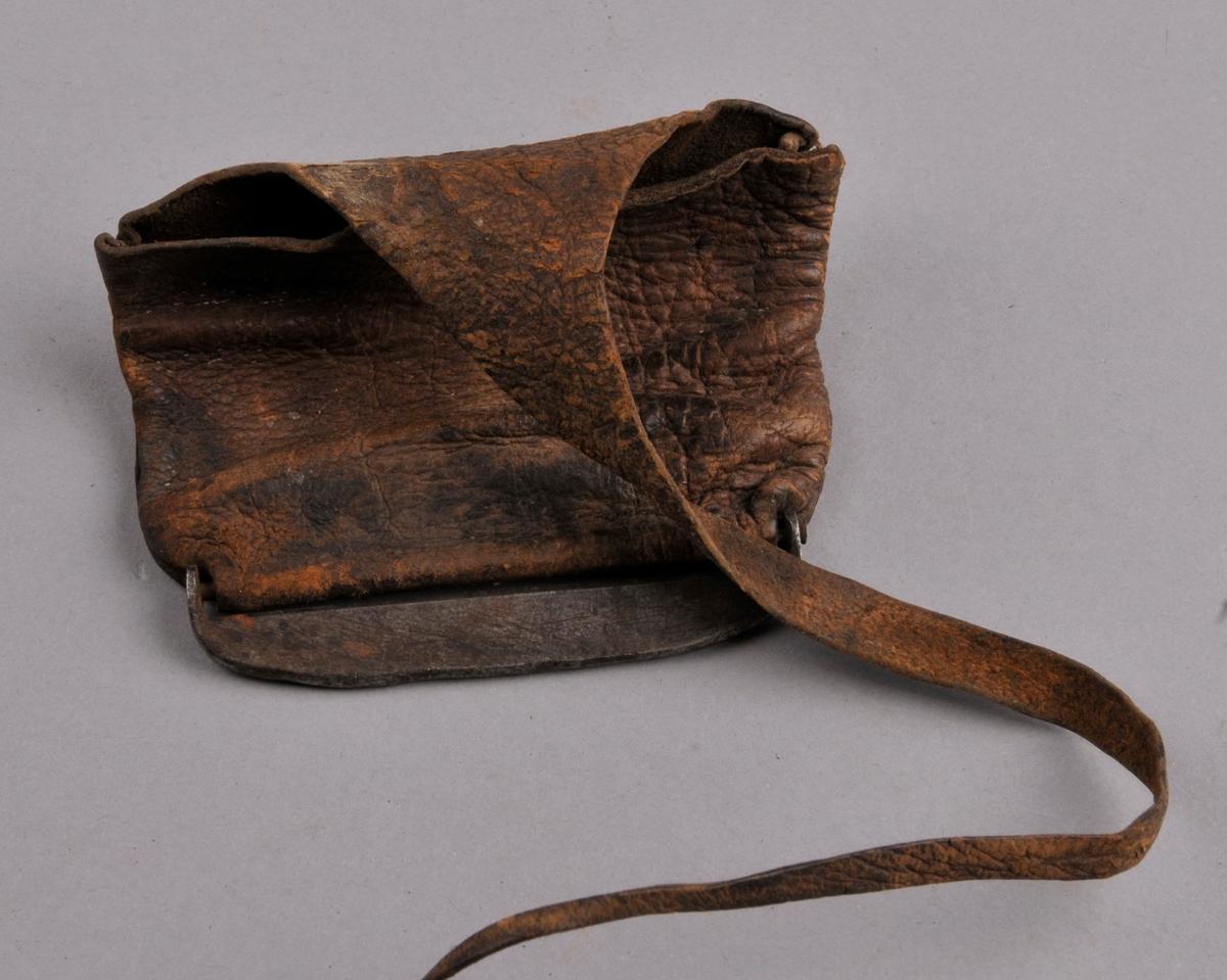 Skinnpung med metallbeslag nederst. (Flint) Pungen er laga av eit stykke skinn som er sydd saman i sidene. Lok med snøring.
