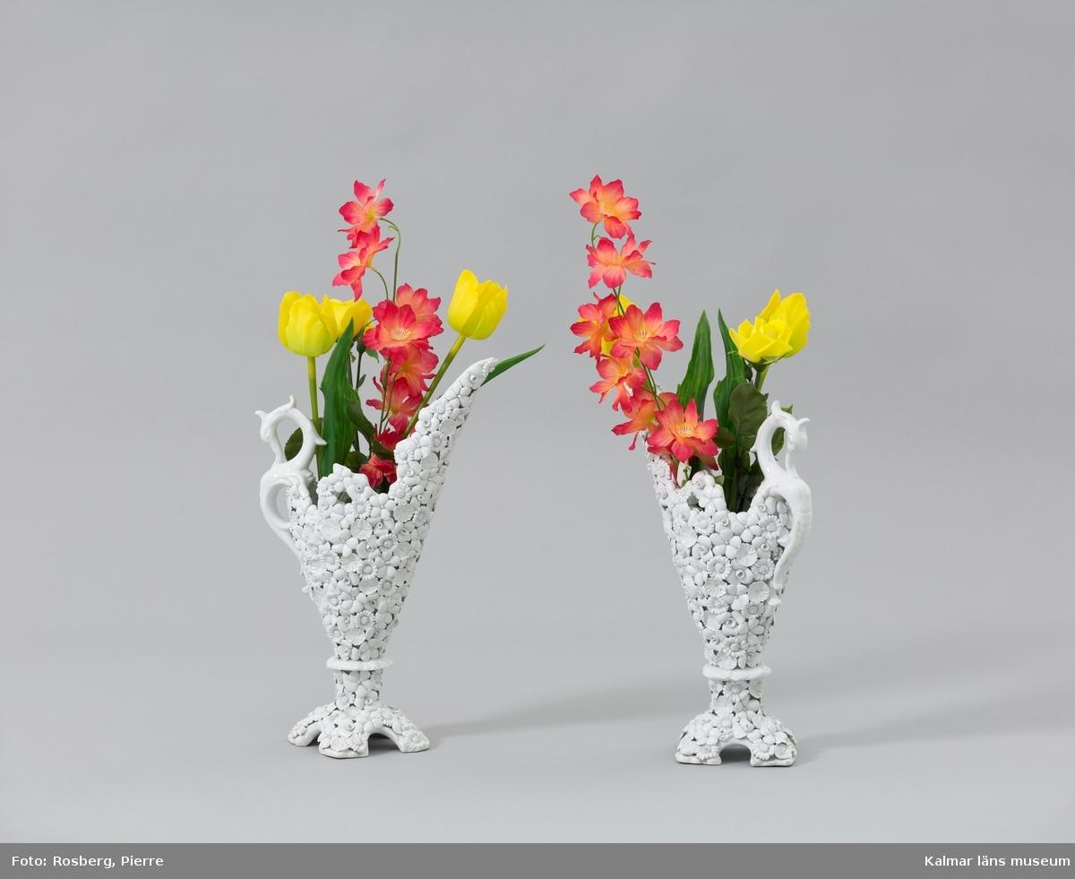 KLM 45619:145:1:1-2. Vas, med plastblomma. Vas (:1) av vitglaserad keramik med ett handtag formad som en sjöhäst. Vasen är formad som en kanna med pip och fot, utsidan är smyckad med blommor och blad. På undersidan en stämpel: ITALY. Till vasen hör ett knippe plastblommor (:2) med bl.a. tulpaner och rosor i gult, rött och grönt.