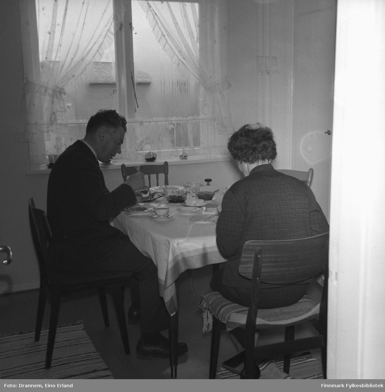 To personer sitter å spiser i Drannems leilighet i Hammerfest. Mannen er Kasper Gabrielsen og damen er Berna Gabrielsen.