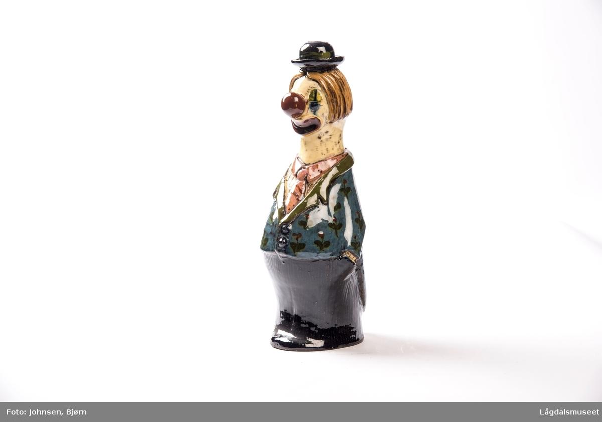 Figuren består av ulike ornamenter som danner klær, og ansikt på en klovn.