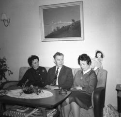 Tre personer sitter i sofaen i stua hjemme hos familien Dran