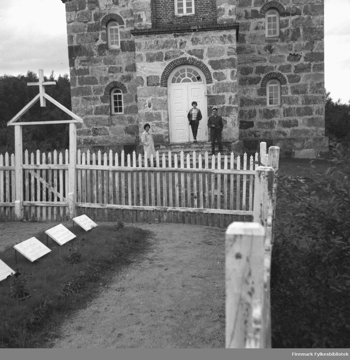 Familien Drannem, Jenny, Turid og Eino fotografert utenfor en murbygning, sannsynligvis en kirke, i Utsjok.