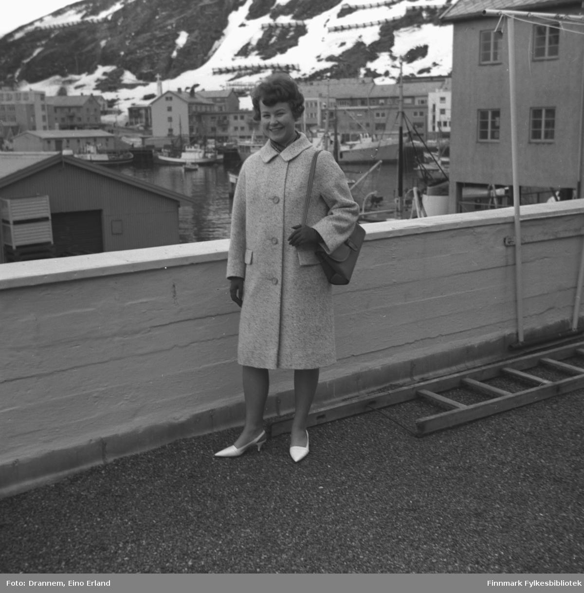 Turid Karikoski poserer for fotografen på verandataket til Tollboden i Hammerfest. I bakgrunnen ses indre havn med bebyggelsen langs Strandgata og fjellsiden til Salen.