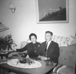 Berna og Kasper Gabrielsen sitter i sofaen hjemme hos famili