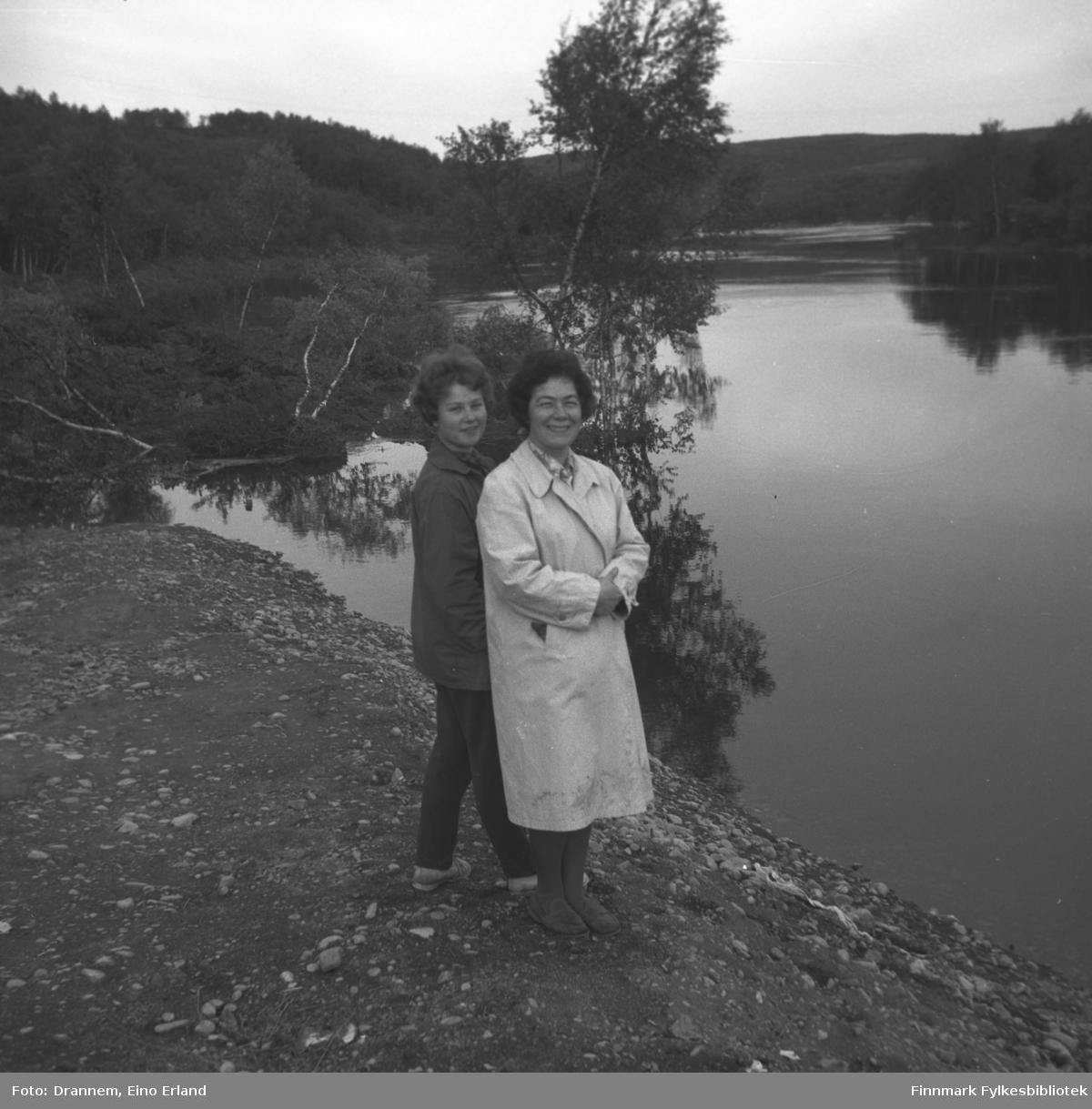 Turid Karikoski og Jenny Drannem fotografert ved bredden av en elv, muligens Neidenelva.