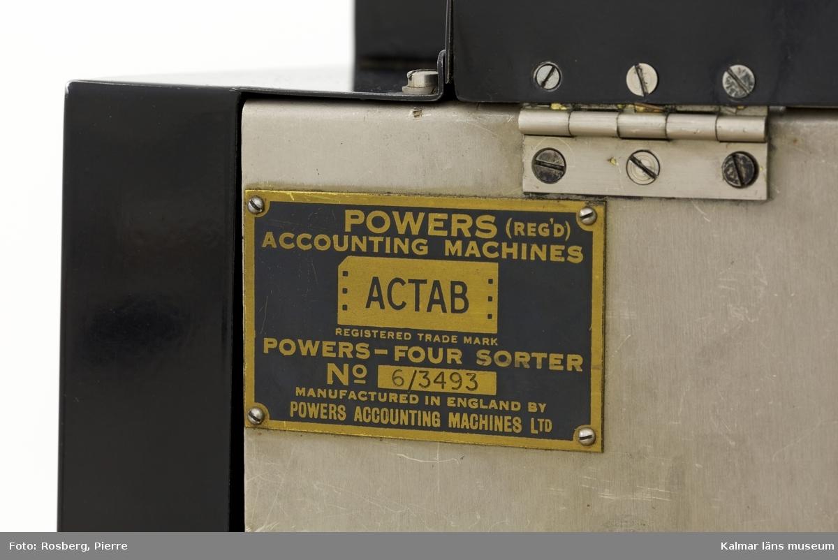 KLM 28585:6. Hålkortsmaskin, sorteringsmaskin. Användes för att sortera hålkorten i önskvärd ordning efter någon av de noteringar som stansats i korten. Till höger matas hålkorten in för att sedan sorteras automatiskt enligt den stansning som maskinen blivit inställd på. Korten hamnar i de olika avläggningsfacken, sammanlagt 12 stycken. 11 av facken är uppmärkta på en glasskiva upp till, A samt 0-9. Maskinen är rektangulär, av svartlackerad metall och brunmålat trä samt detaljer av glas. På vardera kortsida ett handtag. På baksidan en svart elsladd. På maskinen diverse fastskruvade metallskyltar samt ett klistermärke, samtliga med information om tillverkaren och produktionen, bl.a: POWERS SAMAS ACCOUNTING MACHINES ENGLAND samt POWERS-FOUR SORTER. På högra kortsidan en liten metallskylt med instansade siffror: 0264. Till maskinen hör en skyddshuv av grå galon med text i gult: Tillhör Statsverket.