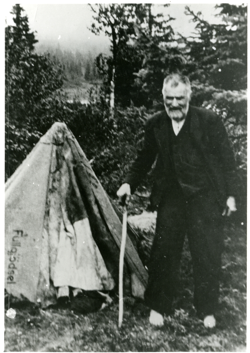 Nub Brager fotografert ute i skogen. Han har en stokk i den ene hånden. I bakgrunnen kan det ses noe som ligner et telt.