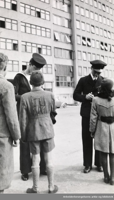 """Serie med fotografier fra okkupasjonsårene og frigjøringsdagene i Oslo, tatt av Ole M. Engelsen..""""Autografjegere. 14 mai 1945. H7-merke på jakka til gutten""""."""