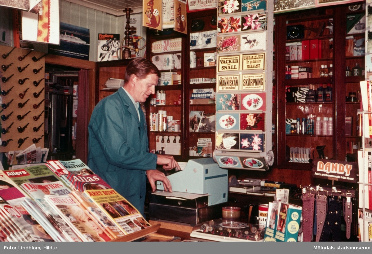 En man står vid kassan i en tobakshandel, troligtvis vid eller i närheten av Gamla Torget i Mölndal, 1970-tal.  För mer information om bilden se under tilläggsinformation.