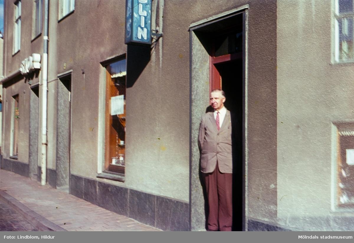 En man står i dörren till Josef Anderssons Porslinsaffär med adress Kvarnbygatan 4 vid Gamla Torget i Mölndal, 1960-1970-tal. I samma hus låg även Rasmussons skoaffär.  För mer information om bilden se under tilläggsinformation.