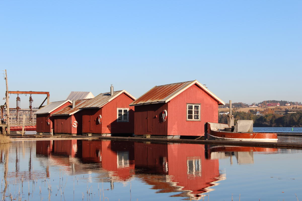 Fire røde hvilebrakker som ligger i elva med en liten bår i forgrunnen