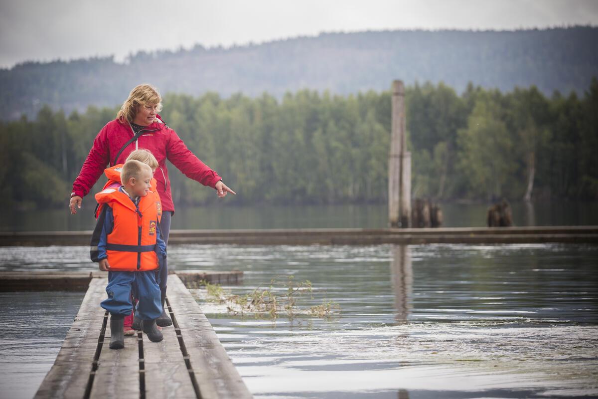 En voksen dame og to små barn går på flåteganer i elva. Begge barna har oransje redningsvester på seg.