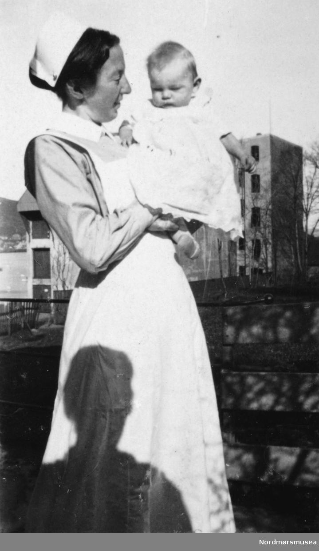 Portrett av en kvinne i sykepleieruniform med et spedbarn på armen. Ukjent hvor, men trolig ved et barnehjem i Bergen. Datering er også ukjent, men trolig omkring 1918 til 1919. Bildet ble gitt til Nordmøre museum av Nelly Rødsand 5. september 1983. Fotoalbumet består av bilder med reg. nr. KMb-1983-024.0049 til KMb-1983-024.0223. Flere bilder fra andre album er å finne på samlingsnummer KMb-1983-024. Fra Nordmøre museums fotosamlinger.