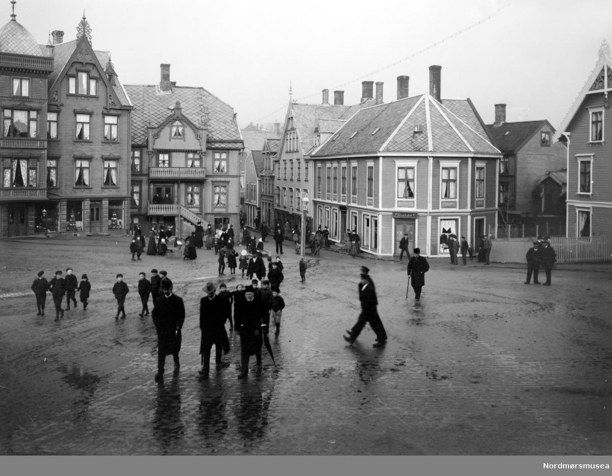 """På bildet ser vi Larsengården (bygget til høyre med skilt over døren, Parcell M. Nr. 75). Lars Larsen, som eide bygget, kjøpte huset 9. august 1873, og solgte det senere til Fosna Mållag 1. september 1909, som rev bygget fra 1797, og reiste et nytt bygg på tomten. Her hadde Fosna Mållag """"Kaffistova"""" hus fra 1910 til de senere solgte bygget den 1. oktober 1930 til Georg Sverdrup. Bygget brente senere ned under bybrannen 28. april 1940, da tyskerne bombet byen. Fra Nordmøre Museum si fotosamling. Kilde: Sverdrups bokhandel, 100 år. 1874 - 1974, side 51 og 52."""