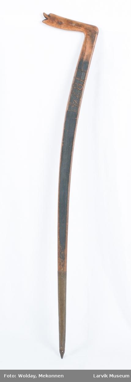 Form: flat, lett svunget. håndtak formet som dyrehode ytterst. høy dobbsko av messing, jernpigg nederst. g.k.: kjeppens form en reminisens fra de gamle bondeøkser
