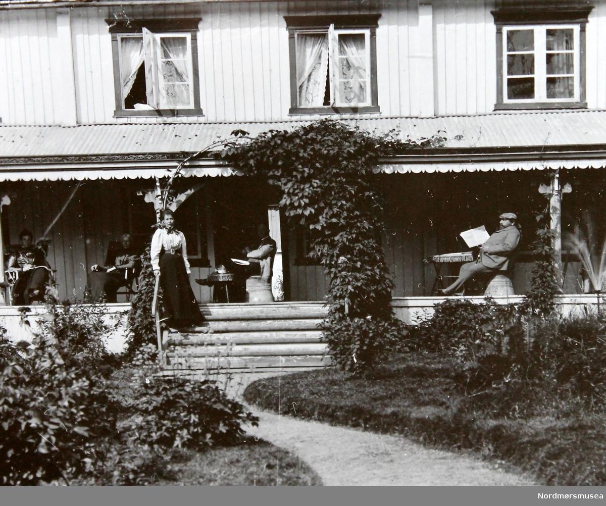 Avbildet motiv er Gjestehuset på Gulla Gård. Vi ser fasaden som vender mot sør. På verandaen sitter to kvinner og to menn, og sentralt i bildet står en kvinne, på trappen ned til hagen. Kvinnen på trappen er Ina Tyndale-Biscoe og mannen som sitter til høyre i bildet og leser en avis er Fleetwood Sandeman.I forgrunnen ser vi deler av hagen. Det er sommer, vinduene står åpne til lufting.